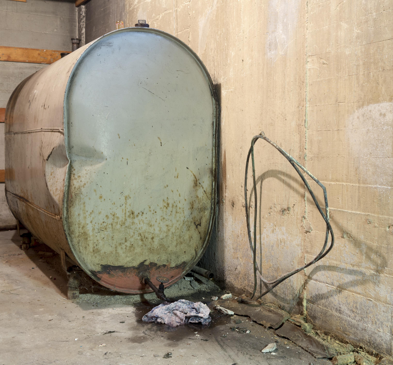 Old oil tank leaking oil in a basement
